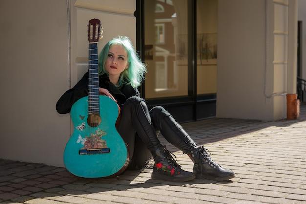 Aan de zijkant van het gebouw zit een straatmuzikant met blauw haar en een blauwe gitaar.