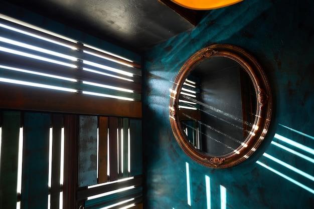 Aan een blauwe muur hangt een antieke ronde spiegel