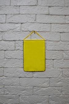 Aan een lichtgekleurde bakstenen muur hangt een gele wimpel. de wimpel is schoon, zonder inscripties of tekeningen. bekleed met een geel-zwarte rand rond de omtrek
