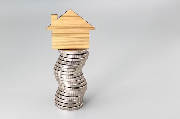 Aan- en verkoop van woningen. hypotheek voor de aankoop van een huis. huurwoning. een klein houten huis staat op een stapel munten. detailopname. ruimte kopiëren. gezinsbesparingen.