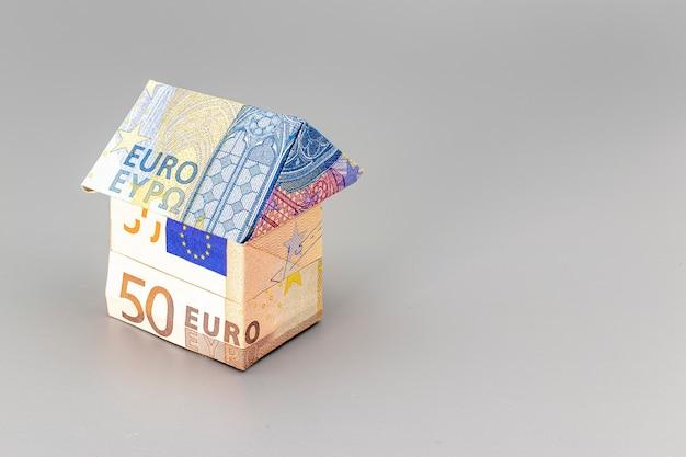 Aan- en verkoop van woningen. hypotheek voor de aankoop van een huis. huurwoning. huis gevouwen van eurobankbiljetten. origami. detailopname. ruimte kopiëren. huisvesting in europa.