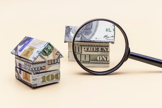 Aan- en verkoop van woningen. hypotheek voor de aankoop van een huis. huurwoning. huizen gevouwen van dollarbiljetten onder een vergrootglas. origami. detailopname. ruimte kopiëren. huisvesting in de vs.