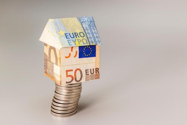 Aan- en verkoop van woningen. hypotheek voor de aankoop van een huis. huurwoning. op een stapel munten staat een huis van euro's. origami. detailopname. ruimte kopiëren. huisvesting in europa.