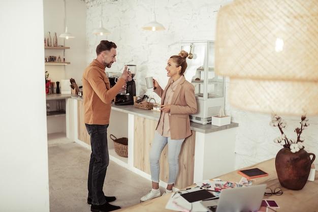 Aan het dollen. knappe man die in de keuken staat en hilarische grappen vertelt aan zijn mooie collega.