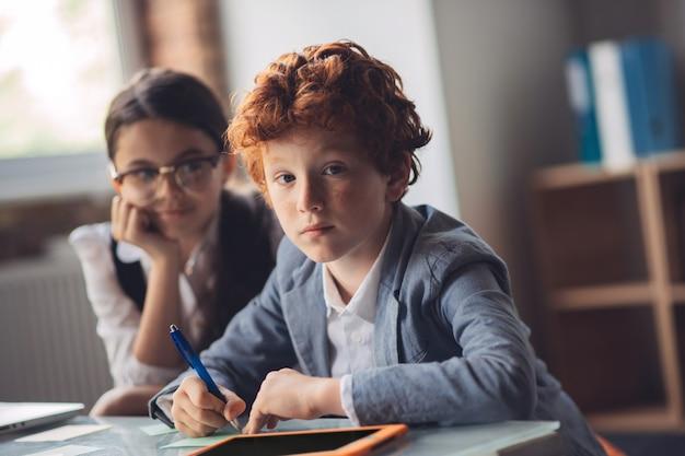 Aan het leren. roodharige jongen studeert met zijn vriend en kijkt attent