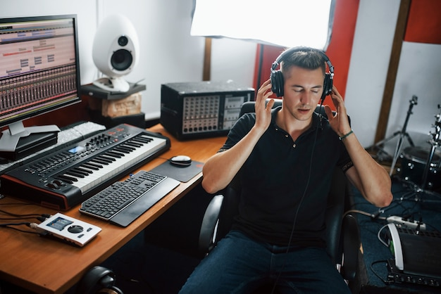 Aan het luisteren naar de muziek. geluidstechnicus in koptelefoon die binnen in de studio werkt en mixt.