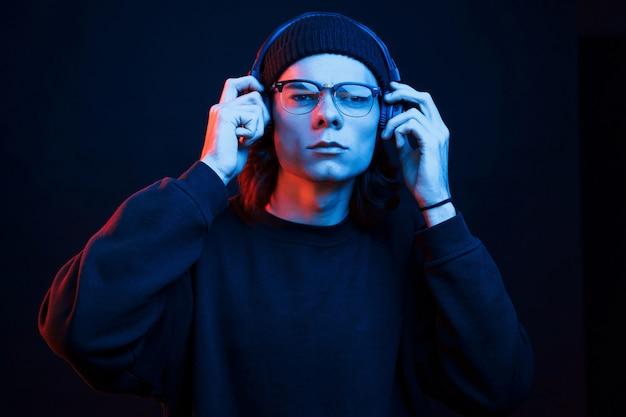 Aan het luisteren naar de muziek. studio opname in donkere studio met neonlicht. portret van ernstige man