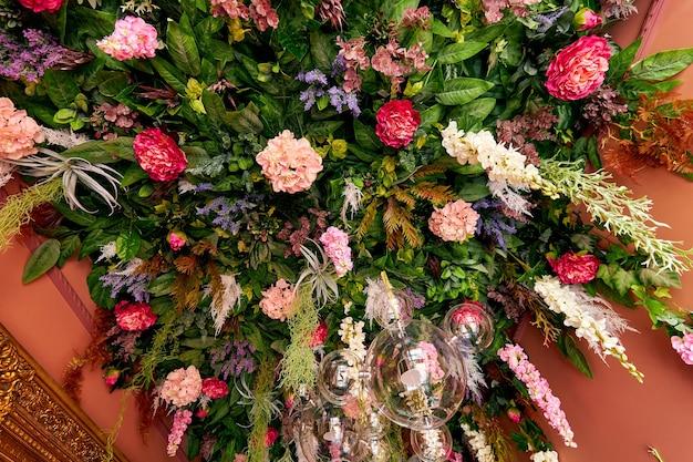 Aan het plafond van het gebouw hangen veel bloemen en planten
