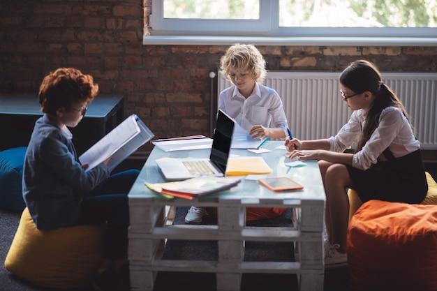 Aan het studeren. drie kinderen studeren samen en kijken betrokken