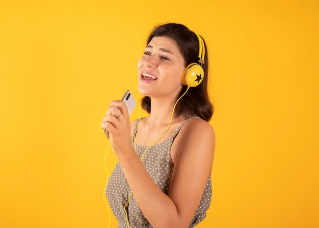 Aan muziek met hoofdtelefoons luisteren en vrouw die, gele ruimte zingen
