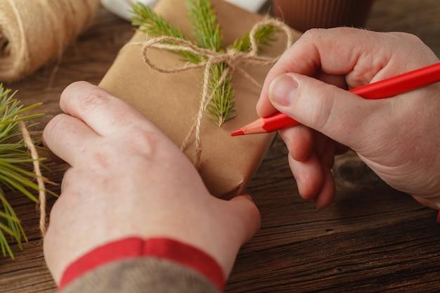 Aan tafel wikkelt kerstcadeautjes. handgemaakt