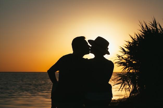 Aanbeden door een verliefd stel aan de kust die bij zonsondergang van elkaar genieten