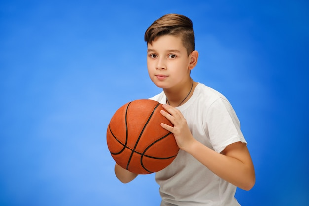 Aanbiddelijk 11 éénjarigenjongenskind met basketbalbal