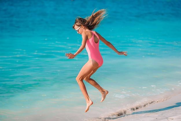Aanbiddelijk actief meisje op strand tijdens de zomervakantie