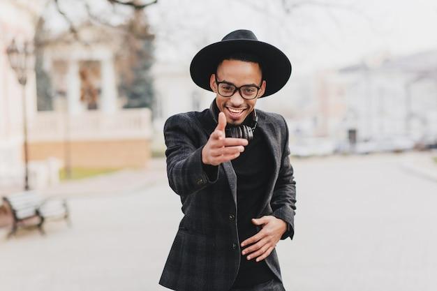 Aanbiddelijk afrikaans mannelijk model wijzende vinger met zelfverzekerde gezichtsuitdrukking. outdoor portret van goed geklede positieve zwarte man.