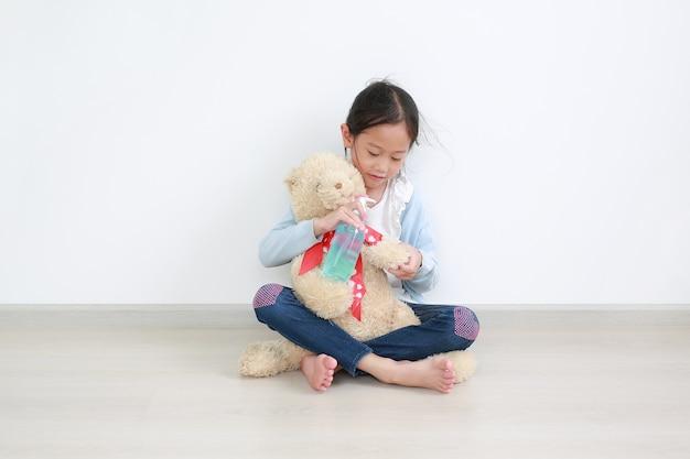 Aanbiddelijk aziatisch klein kindmeisje die alcoholgel van plastic fles voor het schoonmaken van teddybeer toepassen