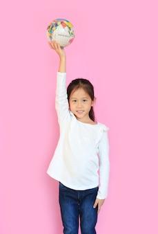 Aanbiddelijk aziatisch klein kindmeisje werpt een wereldbol op het hoofd op met het kijken naar camera geïsoleerd op roze achtergrond.