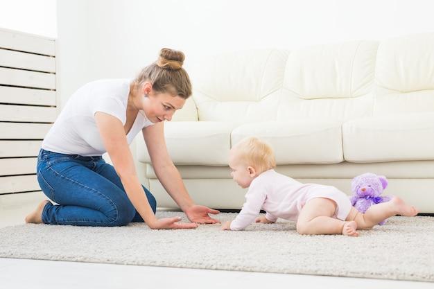 Aanbiddelijk babymeisje dat in witte zonnige ruimte leert kruipen.