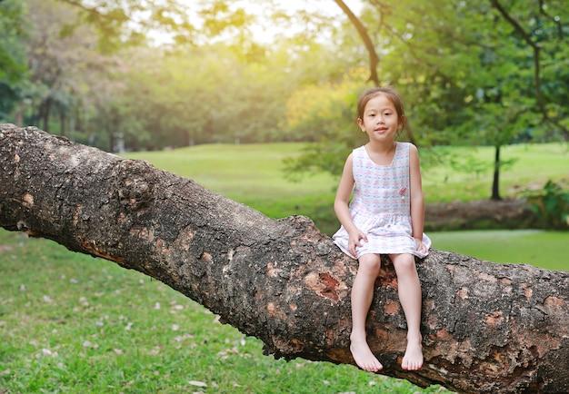 Aanbiddelijk beklimt weinig kindmeisje en rustend op grote boomboomstam in de tuin openlucht.