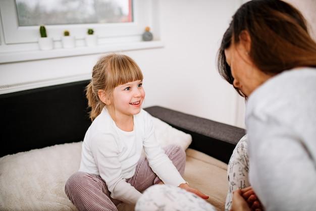Aanbiddelijk blond meisje dat pret met moeder heeft. zittend in pyjama op het bed.