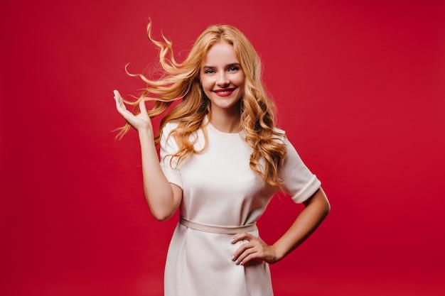 Aanbiddelijk europees meisje dat opwinding uitdrukt. geweldige blonde vrouw in witte jurk.