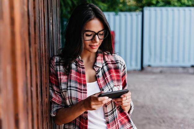 Aanbiddelijk gelooid meisje dat mobiel internet met glimlach gebruikt. openluchtportret van vrolijke donkerbruine vrouwelijke student die zich op straat met telefoon bevindt.
