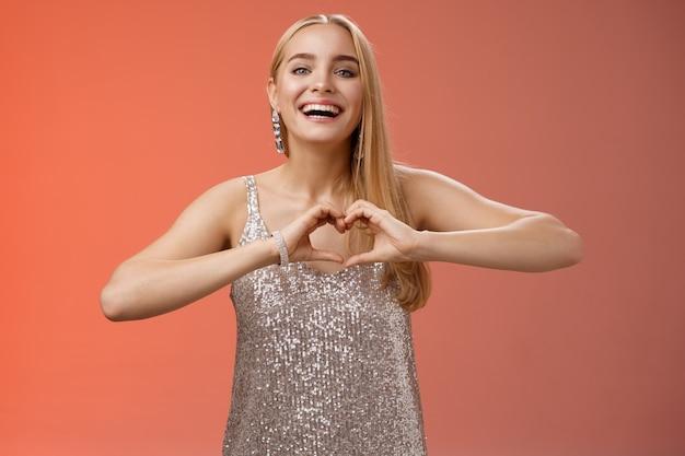 Aanbiddelijk gelukkig charmant mooi blond europees meisje in zilveren kleding uitdrukkelijke positiviteit van de liefde toon hartgebaar sympathie gepassioneerde gevoelens jegens vriend breed glimlachend, rode achtergrond.