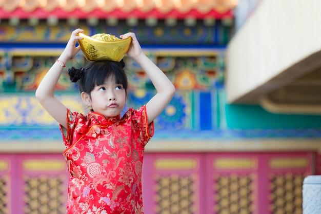 Aanbiddelijk gelukkig chinees meisje dat goudstaaf op chinees nieuwjaar ontvangt