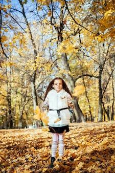 Aanbiddelijk gelukkig meisje dat zich onder de gevallen gekleurde herfstbladeren bevindt die in het de herfstpark spelen