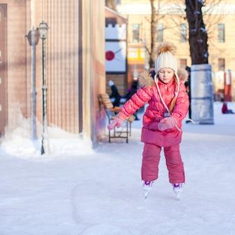 Aanbiddelijk gelukkig meisje die van schaatsen genieten bij de ijsbaan