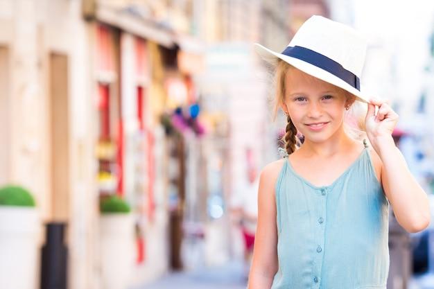 Aanbiddelijk gelukkig meisje in openlucht in europese stad.