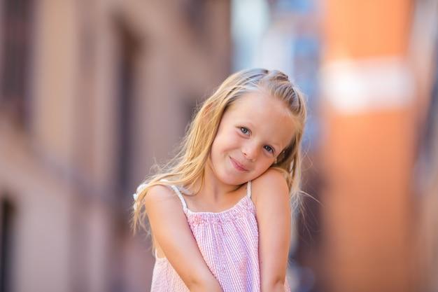 Aanbiddelijk gelukkig meisje in openlucht in italiaanse stad. het portret van kaukasisch jong geitje geniet de zomer van vakantie in rome