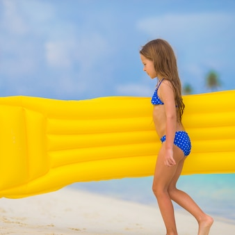 Aanbiddelijk gelukkig meisje met opblaasbare luchtmatras op wit strand