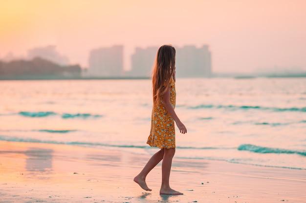 Aanbiddelijk gelukkig meisje op wit strand bij zonsondergang.