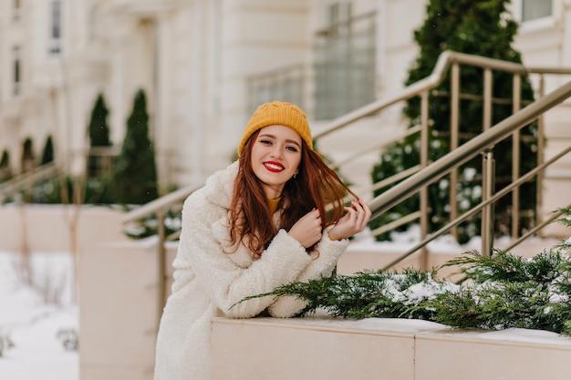 Aanbiddelijk gembermeisje dat in hoed positieve emoties uitdrukt. schitterend vrouwelijk model ontspannen in de winter.