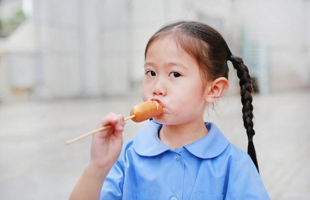 Aanbiddelijk geniet weinig aziatisch kindmeisje in eenvormige school het eten van worst.