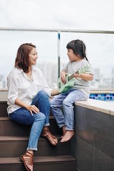 Aanbiddelijk getalenteerd aziatisch meisje dat ukelele speelt en een lied zingt voor haar moeder
