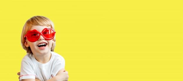 Aanbiddelijk glimlachend weinig die jongen in rode zonnebril in de vorm van lippen op geel wordt geïsoleerd
