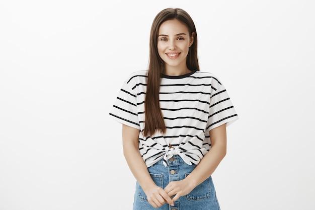 Aanbiddelijk jong bescheiden meisje dat leuk glimlacht kijkt