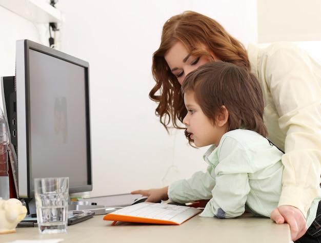 Aanbiddelijk jong geitje en moeder die een computer met behulp van