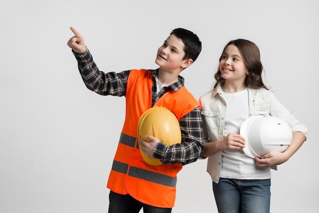 Aanbiddelijk jong jongen en meisje die bouwvakkers houden