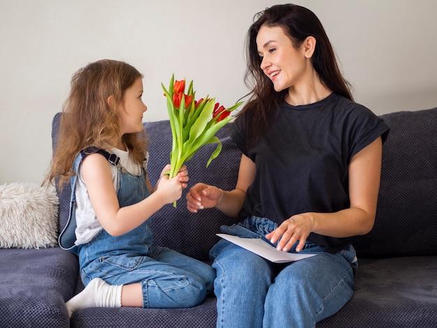 Aanbiddelijk jong meisje dat bloemen geeft aan moeder