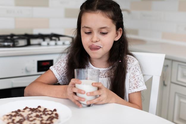 Aanbiddelijk jong meisje dat een melkglas houdt