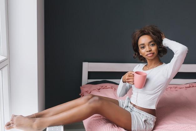 Aanbiddelijk jong meisje dat van ochtend op bed naast venster geniet, koffie, thee in kamer met grijze muur, roze tapijt op ruimte houdt