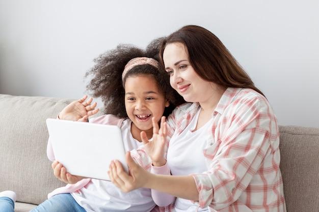 Aanbiddelijk jong meisje die op tekenfilms met moeder letten