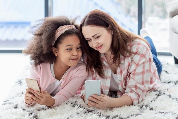Aanbiddelijk jong meisje gelukkig om thuis met moeder te zijn
