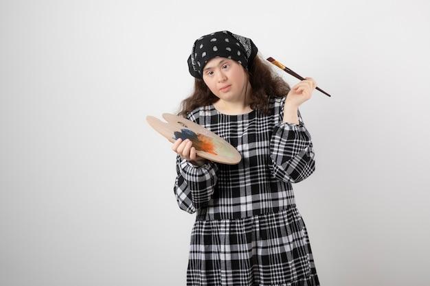 Aanbiddelijk jong meisje met het schilderspalet van de downsyndroomholding.