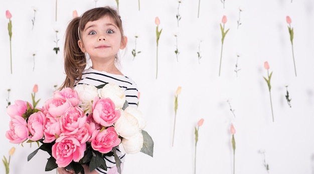 Aanbiddelijk jong meisje met roze boeket