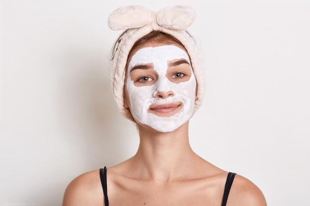Aanbiddelijk jong wijfje met wit gezichtsschoonheidsmasker, meisje dat met haarband schoonheidsprocedure doet