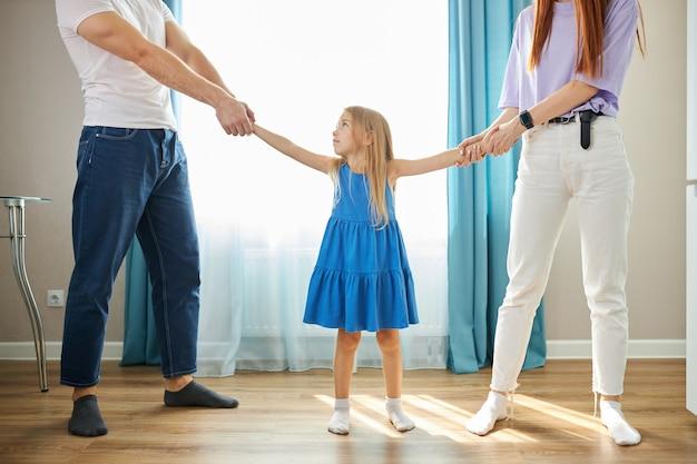 Aanbiddelijk kaukasisch kindmeisje tussen depressieve ouders